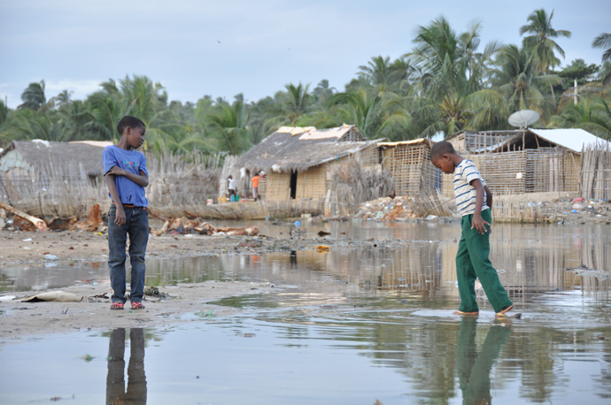 A boy in Paquitiquete, the lowest lying neighborhood in Pemba city, walks through a wet section to reach his friend in July 2014. People in Paquitiquete are used to the flooding as a result of tidal changes. Gradual sea level rise and extreme rain keep many houses wet -- the wait for the water to retreat and for houses to dry can be long. / Cristina Miranda, USAID