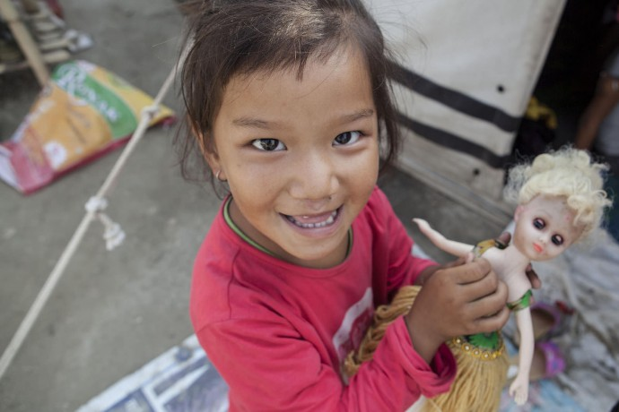 A young girl plays with her doll outside her family's tent at Camp Hope. More than 330 families from the Sindhupalchowk district are taking temporary shelter at the camp. / Kashish Das Shrestha/USAID