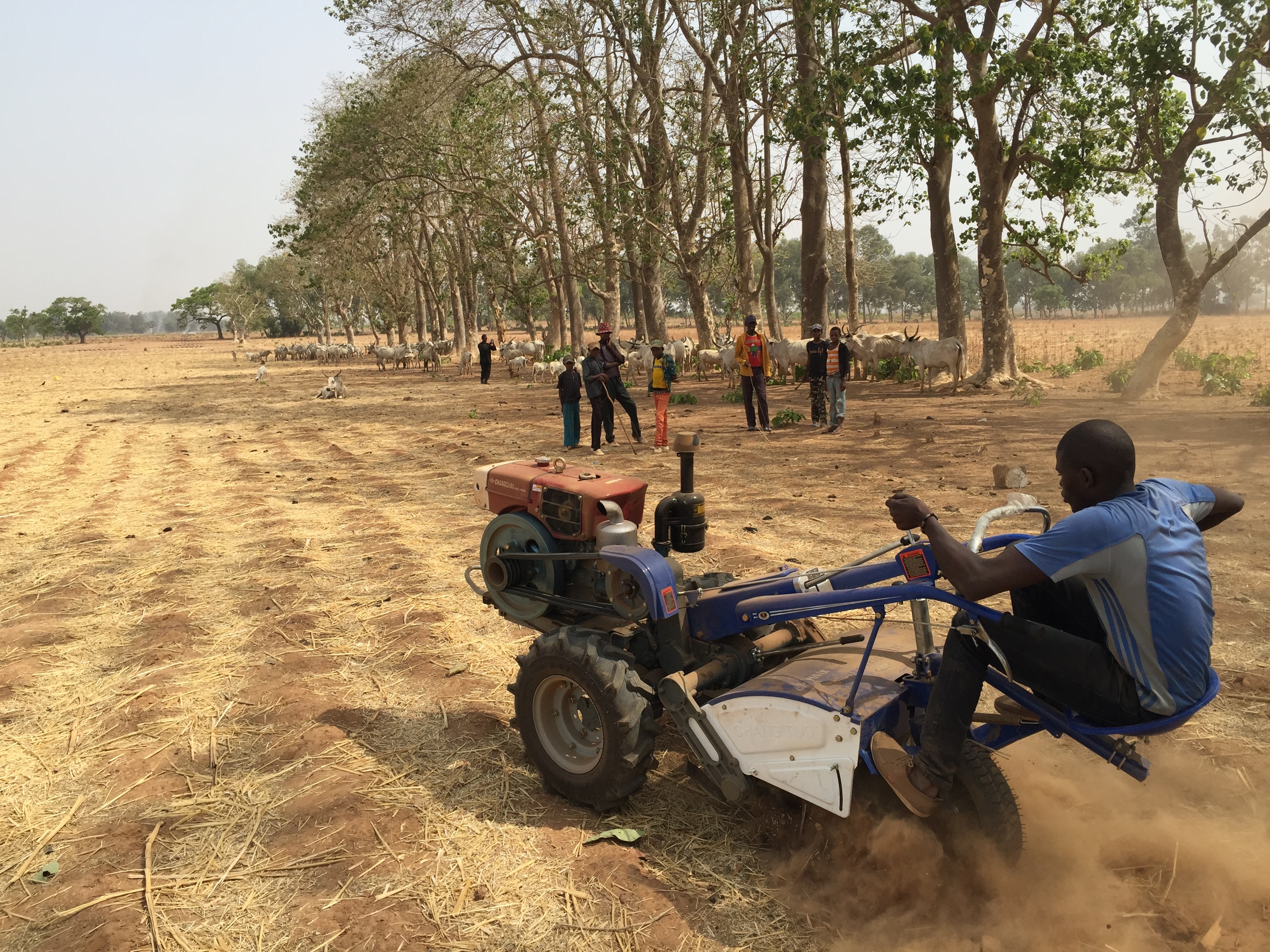 Field engineer, Mathew, stress tests Smart Tractor at test farm in Kaduna as kids from nearby village look. / Jehiel Oliver.